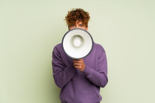 Junger afroamerikanermann über lokalisierter grüner wand schreiend durch ein megaphon
