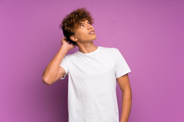 Junger afroamerikanermann über lokalisierter purpurroter wand eine idee denkend