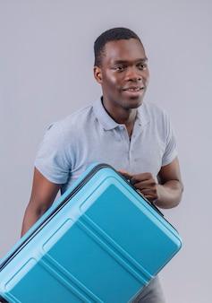 Junger afroamerikanerreisender mann im grauen poloshirt, der blauen koffer hält, der lächelnd beiseite schaut