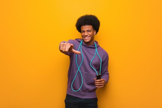 Junger afroamerikanersportmann, der ein seilspringen nett und das lächeln zeigt auf front hält