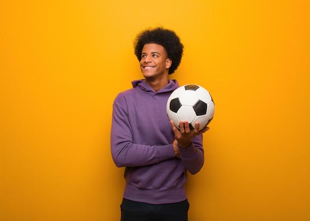 Junger afroamerikanersportmann, der einen fußball lächelt überzeugt und die arme kreuzt und oben schaut hält