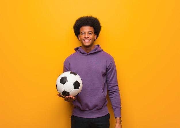 Junger afroamerikanersportmann, der einen fußball nett mit einem großen lächeln hält