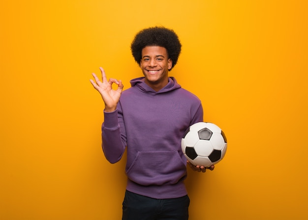 Junger afroamerikanersportmann, der einen fußball nett und überzeugt hält, okaygeste tuend