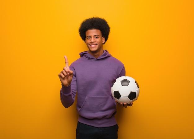 Junger afroamerikanersportmann, der einen fußball zeigt nummer eins hält
