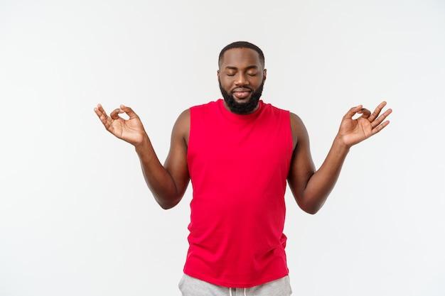 Junger afroamerikanersportmann meditieren isolat über grau.
