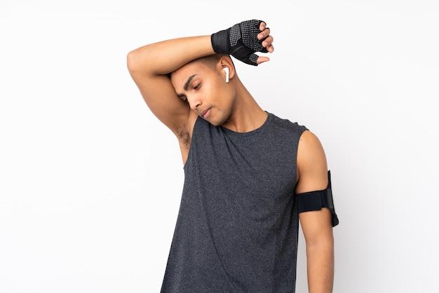 Junger afroamerikanersportmann über lokalisierter weißer wand mit müdem ausdruck