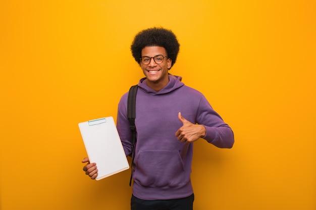 Junger afroamerikanerstudentenmann, der ein klemmbrett lächelt und angehoben daumen hält