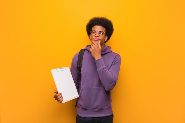 Junger afroamerikanerstudentenmann, der ein klemmbrett zweifelnd und verwirrt hält
