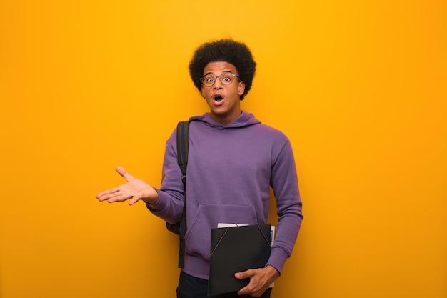 Junger afroamerikanerstudentenmann, der einen sieg oder einen erfolg feiert