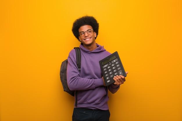 Junger afroamerikanerstudentenmann, der einen taschenrechner lächelt überzeugt und die arme kreuzt und oben schaut hält