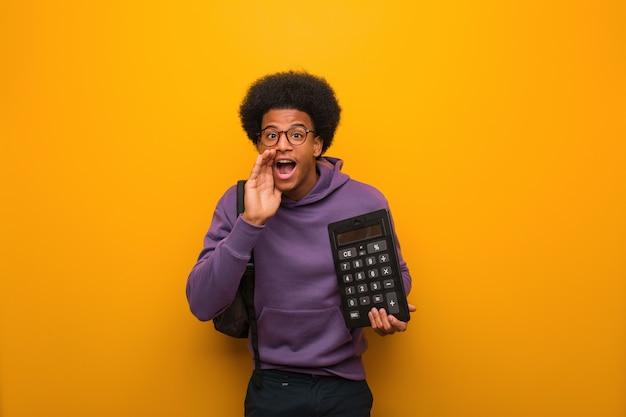 Junger afroamerikanerstudentenmann, der einen taschenrechner schreit etwas glücklich zur front hält