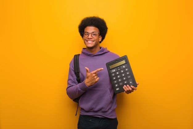 Junger afroamerikanerstudentenmann, der einen taschenrechner zeigt auf die seite mit dem finger hält