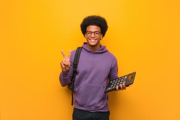 Junger afroamerikanerstudentenmann, der einen taschenrechnerspaß hält und eine geste des sieges tuend glücklich ist
