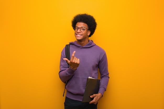 Junger afroamerikanerstudentenmann, der einlädt zu kommen