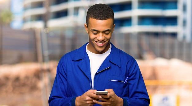 Junger afroamerikanischer arbeitskraftmann, der eine mitteilung mit dem mobile in einer baustelle sendet