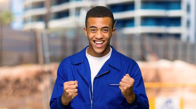 Junger afroamerikanischer arbeitskraftmann, der einen sieg in siegerposition in einer baustelle feiert
