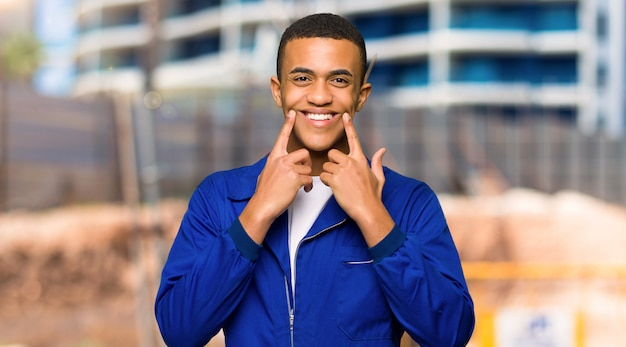 Junger afroamerikanischer arbeitskraftmann, der mit einem glücklichen und angenehmen ausdruck in einer baustelle lächelt