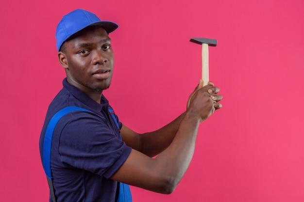 Junger afroamerikanischer baumeistermann, der bauuniform und kappenhaltehammer trägt, der stehend auf lokalisiertem rosa trifft