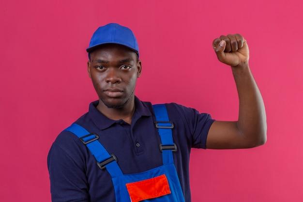 Junger afroamerikanischer baumeistermann, der bauuniform und mütze trägt, die faust mit dem selbstbewussten und ernsten ausdruck, der auf rosa steht, anhebt