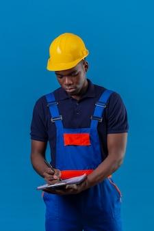 Junger afroamerikanischer baumeistermann, der bauuniform und sicherheitshelm hält, die klemmbrett hält, das notizen mit stift macht, der auf blau steht