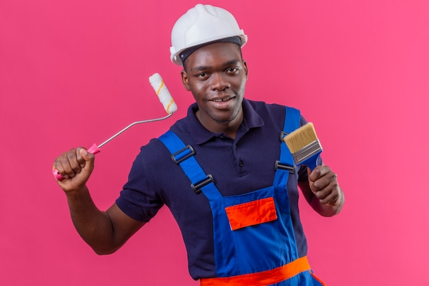Junger afroamerikanischer baumeistermann, der bauuniform und sicherheitshelm hält farbroller und pinsel, die fröhlich auf rosa stehend lächeln