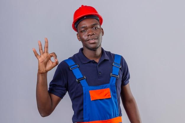Junger afroamerikanischer baumeistermann, der bauuniform und sicherheitshelm mit lächeln auf gesicht trägt, das ok zeichen stehend tut
