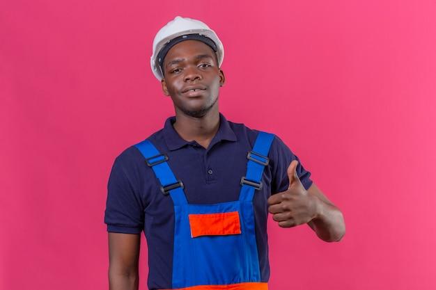 Junger afroamerikanischer baumeistermann, der bauuniform und sicherheitshelm mit lächeln auf gesicht trägt, zeigt daumen oben stehend auf rosa