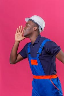 Junger afroamerikanischer baumeistermann, der bauuniform und sicherheitshelm schreit, ruft jemanden mit hand nahe mund, der auf rosa steht