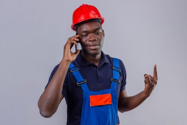 Junger afroamerikanischer baumeistermann, der bauuniform und sicherheitshelm spricht, der auf handy spricht, das steinsymbol lächelnd stehend macht