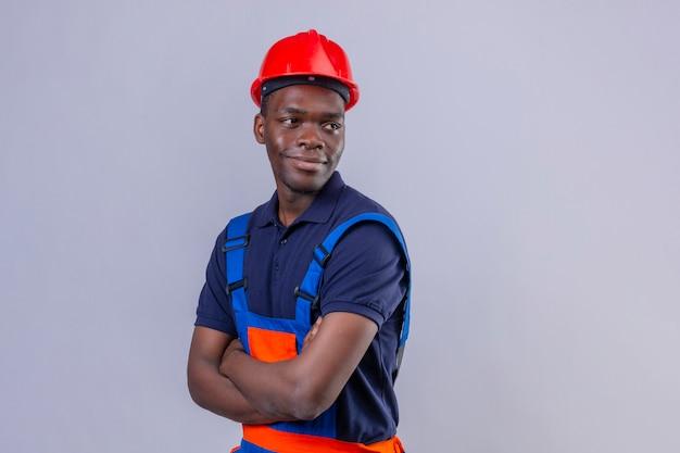 Junger afroamerikanischer baumeistermann, der bauuniform und sicherheitshelm steht, die mit verschränkten armen stehen und lächelndes freundliches stehen beiseite schauen