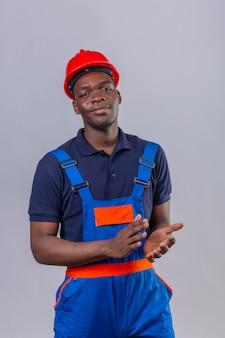 Junger afroamerikanischer baumeistermann, der bauuniform und sicherheitshelm trägt, applaudiert mit zuversichtlichem lächeln auf gesicht stehend