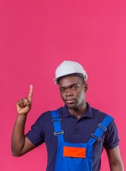 Junger afroamerikanischer baumeistermann, der bauuniform und sicherheitshelm trägt, der mit der warnung des fingers oben der gefahr auf lokalisiertem rosa steht