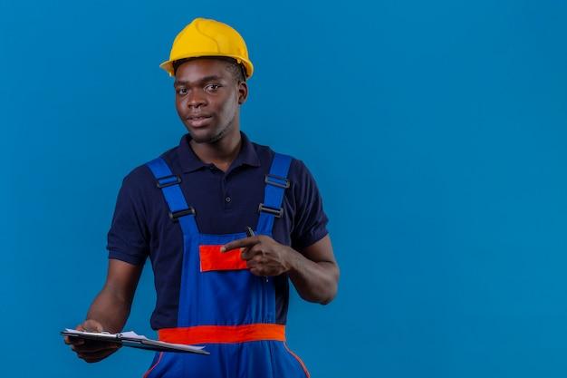 Junger afroamerikanischer baumeistermann, der bauuniform und sicherheitshelm trägt, der mit klemmbrett steht, das mit zeigefinger mit zuversichtlichem lächeln darauf zeigt