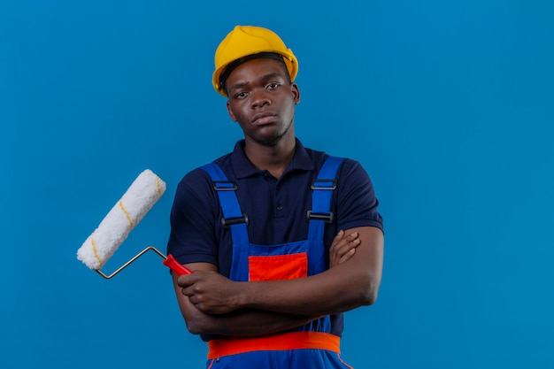 Junger afroamerikanischer baumeistermann, der bauuniform und sicherheitshelm trägt, der mit verschränkten armen auf brust hält farbroller mit stirnrunzeln missfiel
