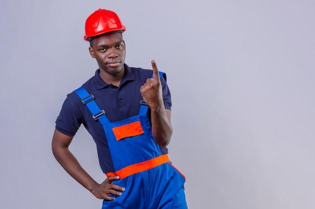 Junger afroamerikanischer baumeistermann, der bauuniform und sicherheitshelm trägt, der mit zeigefinger zeigt, der nummer eins zeigt, das selbstbewusst steht