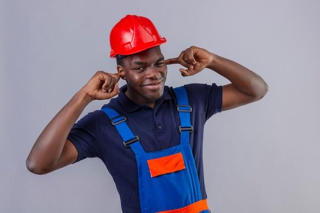 Junger afroamerikanischer baumeistermann, der bauuniform und sicherheitshelm trägt, der ohren mit den fingern mit genervtem ausdruck für das geräusch der stehenden lauten geräusche kegelt