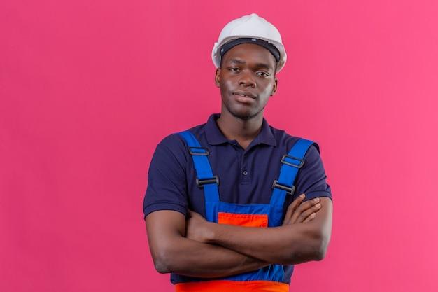 Junger afroamerikanischer baumeistermann, der bauuniform und sicherheitshelm trägt, die mit verschränkten armen auf brust stehen, die auf lokalisiertem rosa zuversichtlich schauen