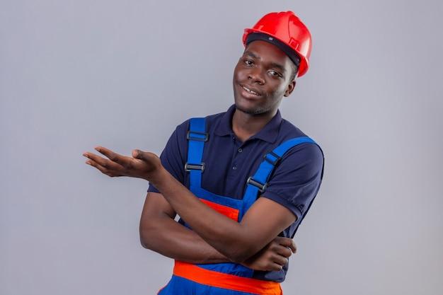Junger afroamerikanischer baumeistermann, der bauuniform und sicherheitshelm trägt, zeigt mit handfläche mit lächelndem lächeln