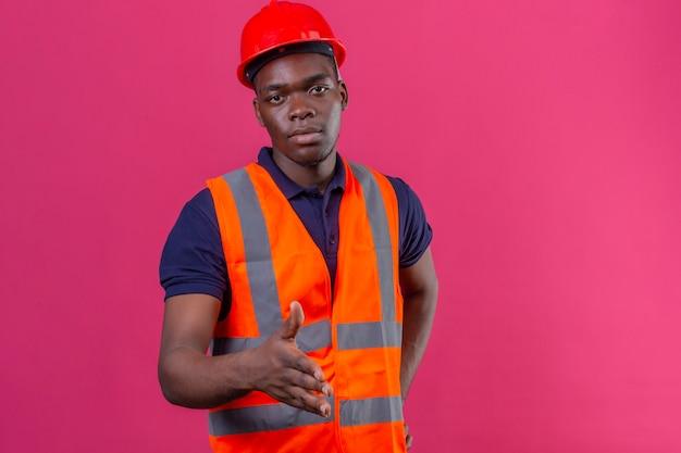 Junger afroamerikanischer baumeistermann, der bauuniform und sicherheitshelm trägt