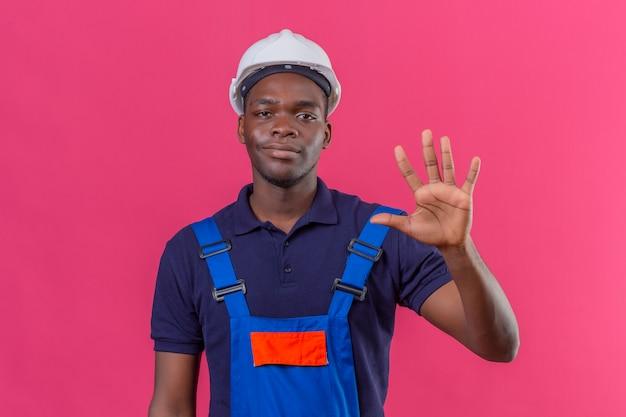 Junger afroamerikanischer baumeistermann, der bauuniform und sicherheitshelm zeigt und mit den fingern nummer fünf zeigt, während er zuversichtlich auf isoliertem rosa lächelt