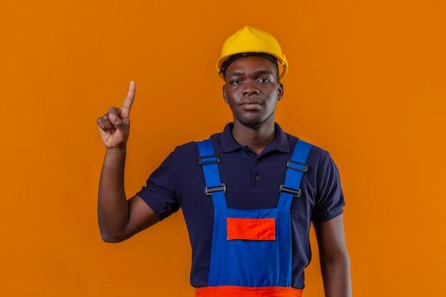 Junger afroamerikanischer baumeistermann, der bauuniform und sicherheitshelm zeigt und mit finger nummer eins zeigt, der zuversichtlich auf isoliertem rosa schaut