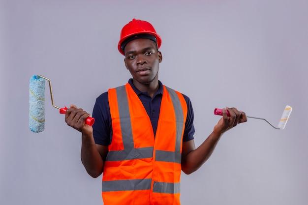 Junger afroamerikanischer baumeistermann, der bauweste und sicherheitshelm hält, der farbroller und pinsel hält, die mit verwirrtem ausdruck mit armen und erhobenen händen stehen
