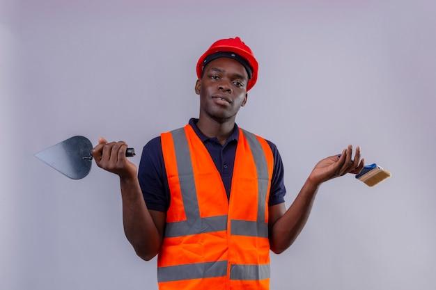 Junger afroamerikanischer baumeistermann, der bauweste und sicherheitshelm hält, der spachtel und pinsel hält, die mit verwirrtem ausdruck mit armen und händen erhoben stehen