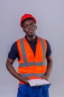 Junger afroamerikanischer baumeistermann, der bauweste und sicherheitshelm hält, die klemmbrett hält, das sicher stehend schaut