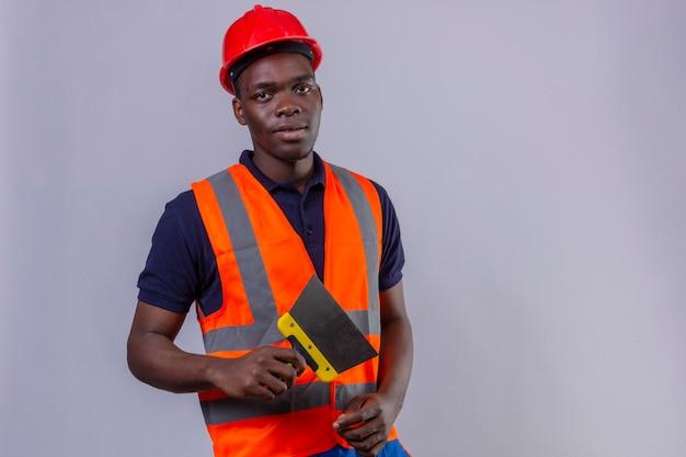 Junger afroamerikanischer baumeistermann, der bauweste und sicherheitshelm hält kittmesser mit ernstem gesichtsstand trägt