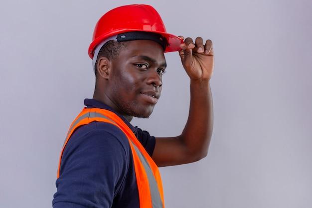 Junger afroamerikanischer baumeistermann, der bauweste und sicherheitshelm mit dem selbstbewussten lächeln trägt, das helm berührt