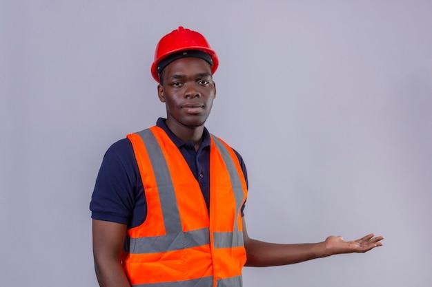 Junger afroamerikanischer baumeistermann, der bauweste und sicherheitshelm mit ernstem gesicht trägt, das mit hand und handfläche auf lokalisiertem weiß präsentiert