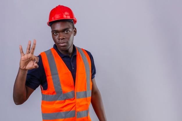 Junger afroamerikanischer baumeistermann, der bauweste und sicherheitshelm mit ernstem gesicht trägt, das ok zeichen stehend tut