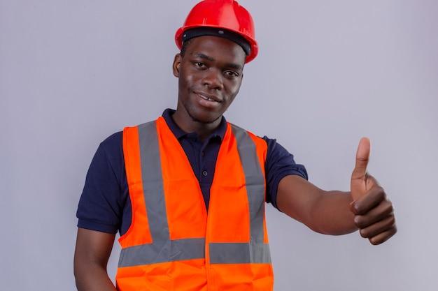 Junger afroamerikanischer baumeistermann, der bauweste und sicherheitshelm mit lächeln auf gesicht trägt, das daumen oben stehend zeigt