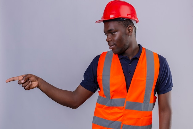 Junger afroamerikanischer baumeistermann, der bauweste und sicherheitshelm trägt, der beiseite schaut und mit dem finger auf die seite steht, die steht